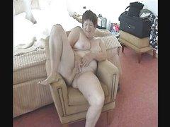 Толстая дама на кресле, приподняв правую ногу дрочит зрелую киску для видео