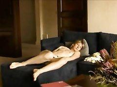 На чёрном диване в любительском порно страждущая леди мастурбирует клитор