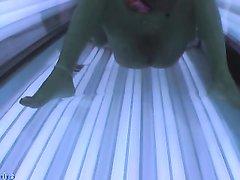 В солярии скрытая камера снимает загорелую и фигурную красотку на видео